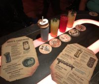 star wars galaxy's edge oga cantina drinks, menu, and coasters on the table.