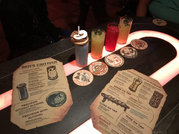 Oga's Cantina drinks, menus, and souvenir coasters on a table at this Star Wars Galaxy's Edge restaurant.