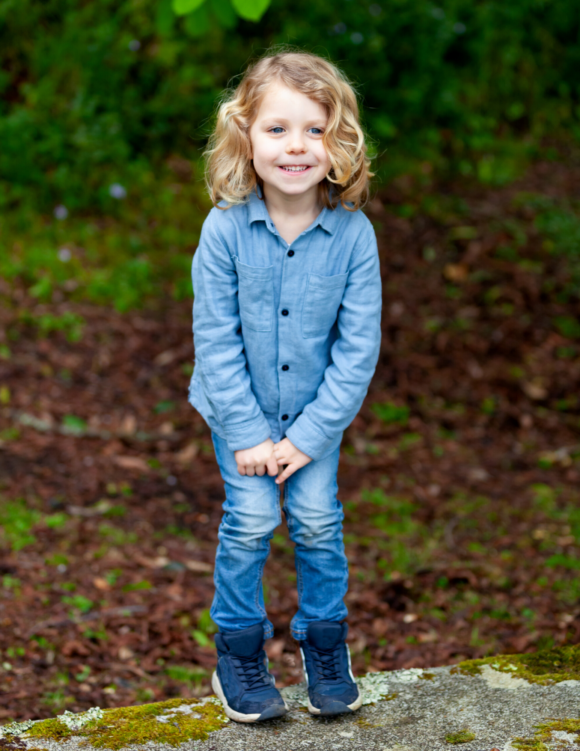girl stands with legs together because she needs to pee in the woods.