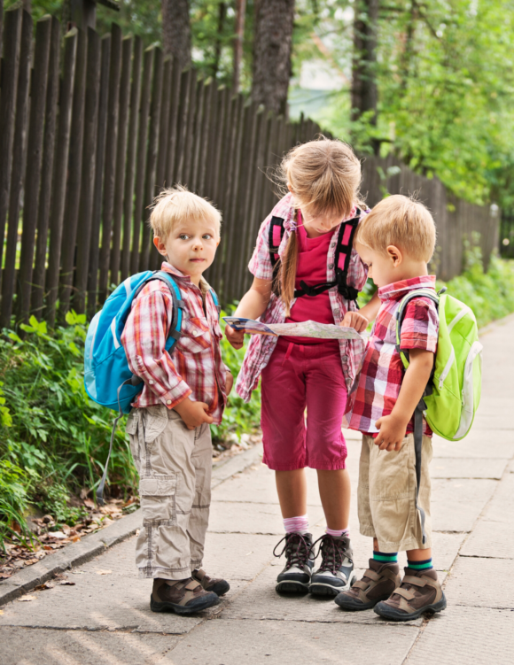 3 kids stand together on a sidewalk discussing going potty outdoors.
