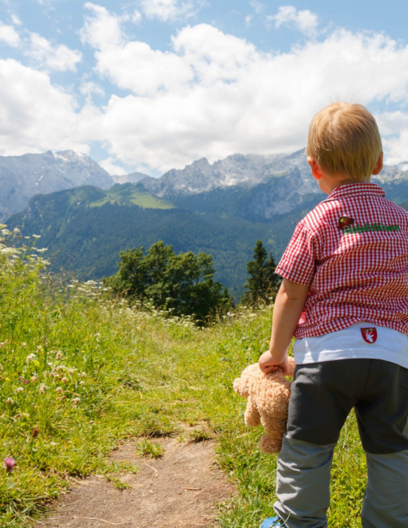 boy stands on grass looking towards the mountain