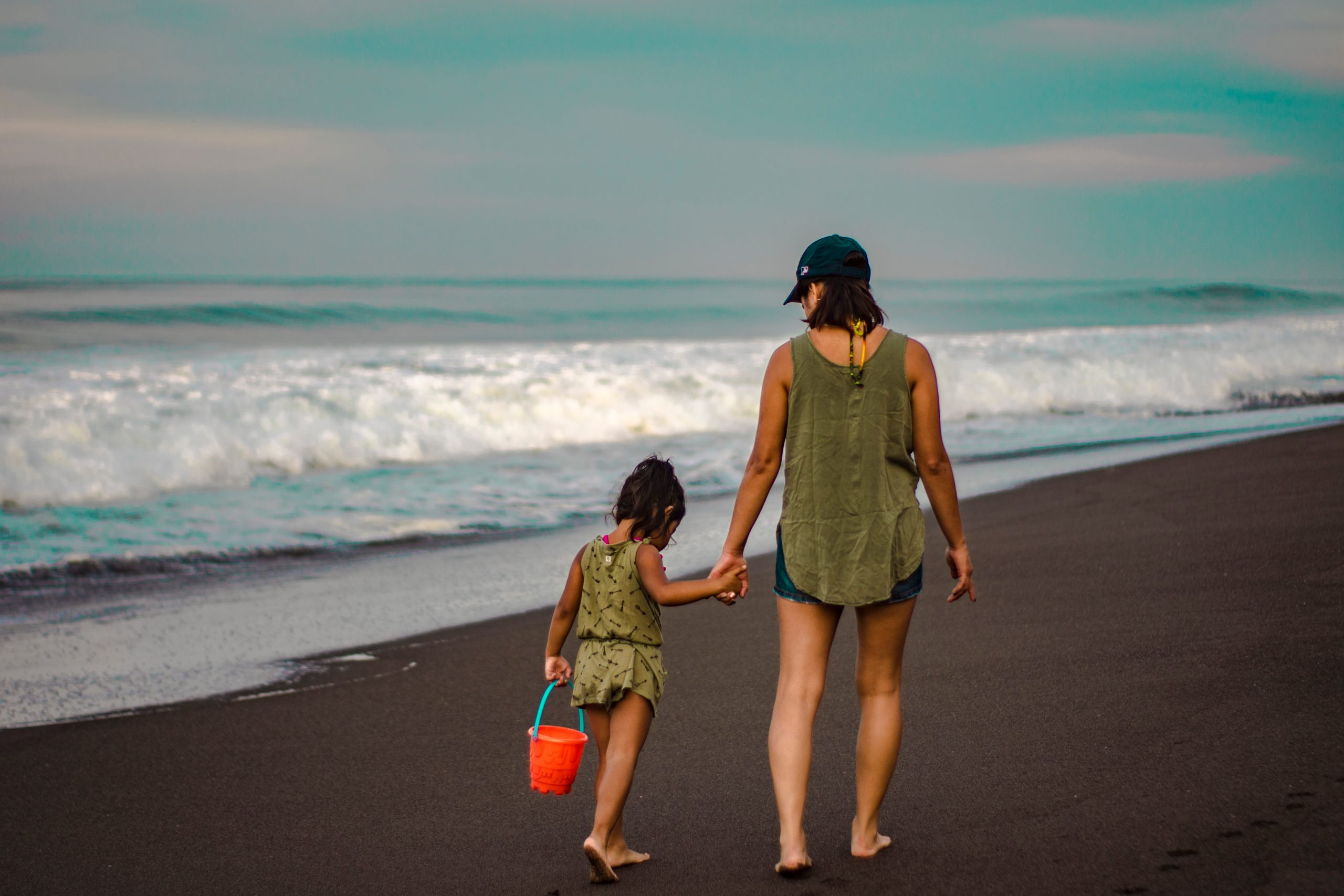 Canva-Back-view-Photo-of-Woman-and-Child-Holding-Hands-While-Walking-on-Beach