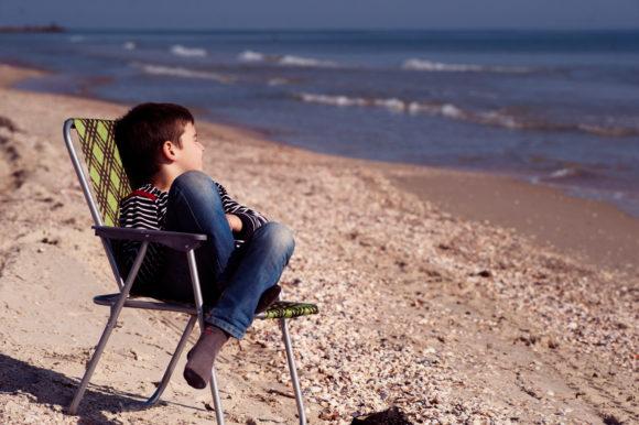 social distancing at beaches boy sits in a beach chair