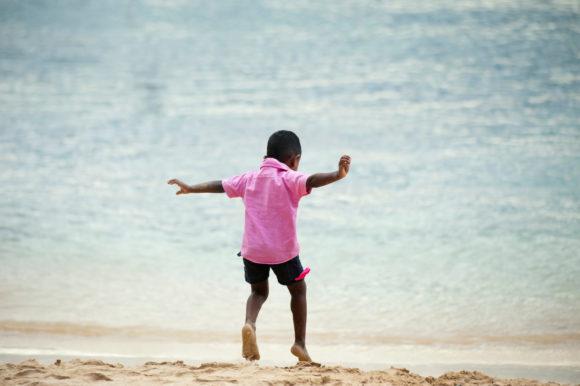 Boy-Wearing-Pink-Collared-Shirt-Running-on-beach