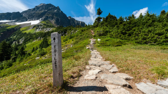 A stone toilet sign points to a path ahead into the forested mountains.