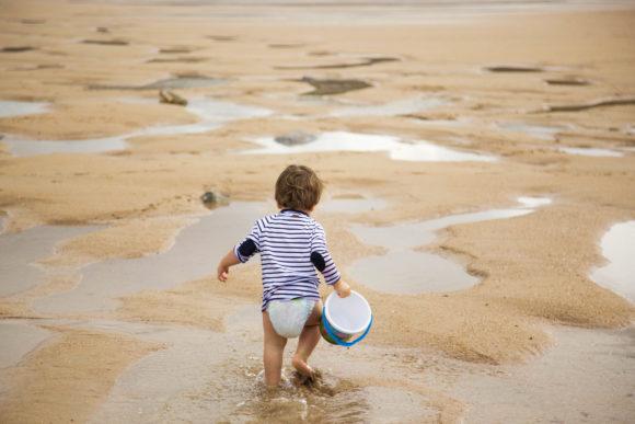 Canva-Toddler-Walking-on-Shoreline