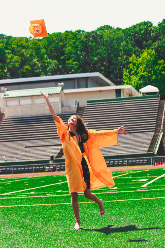 High school graduate poses for picture on football field