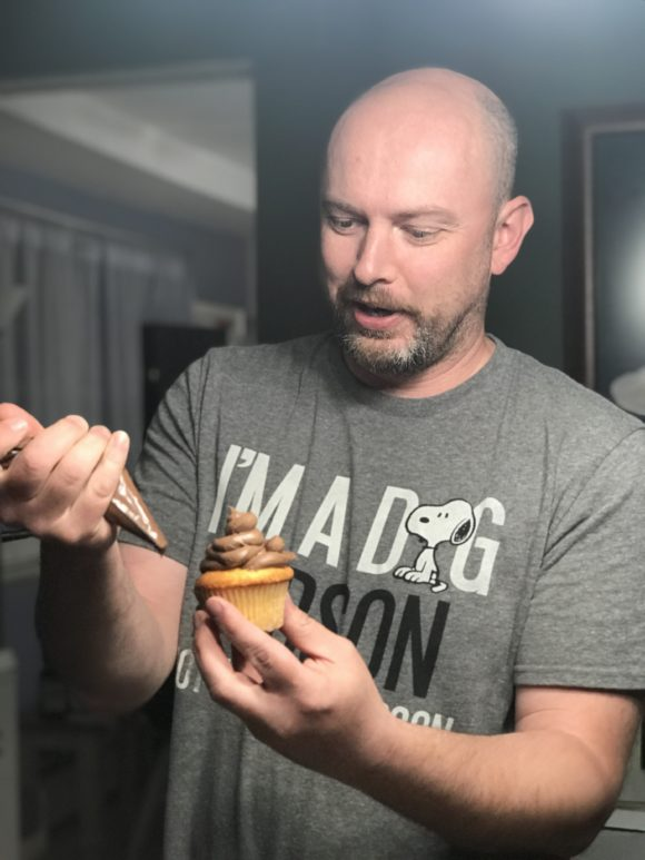 A dad decorates a vanilla cupcake with chocolate icing.