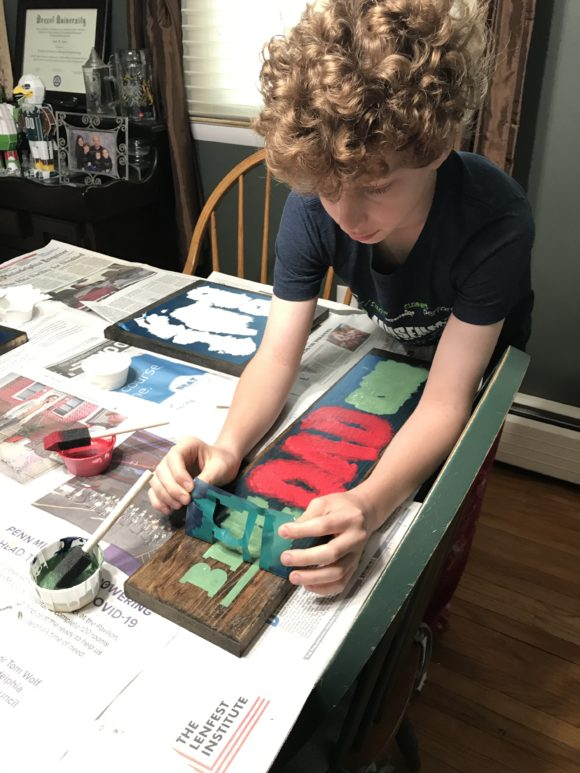 boy peels stencil back from a DIY paint kit from Board and Brush Red Bank