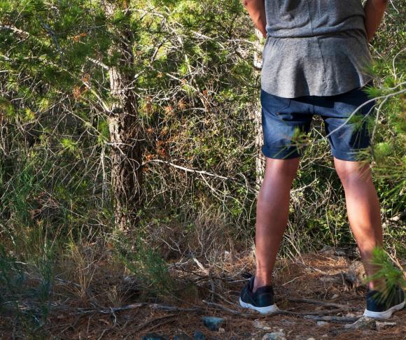 man pees in woods