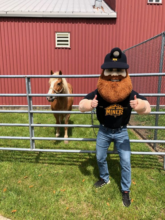 Sussex County Miners mascot poses with a horse.