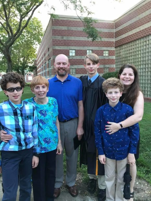 family poses with middle school graduate