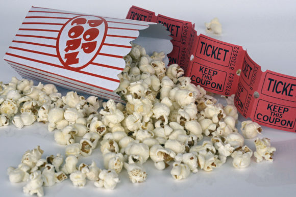 a popcorn bucket spilled over with movie tickets
