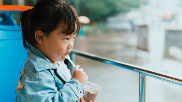 Asian child sits outside to eat a cup of chocolate ice cream.