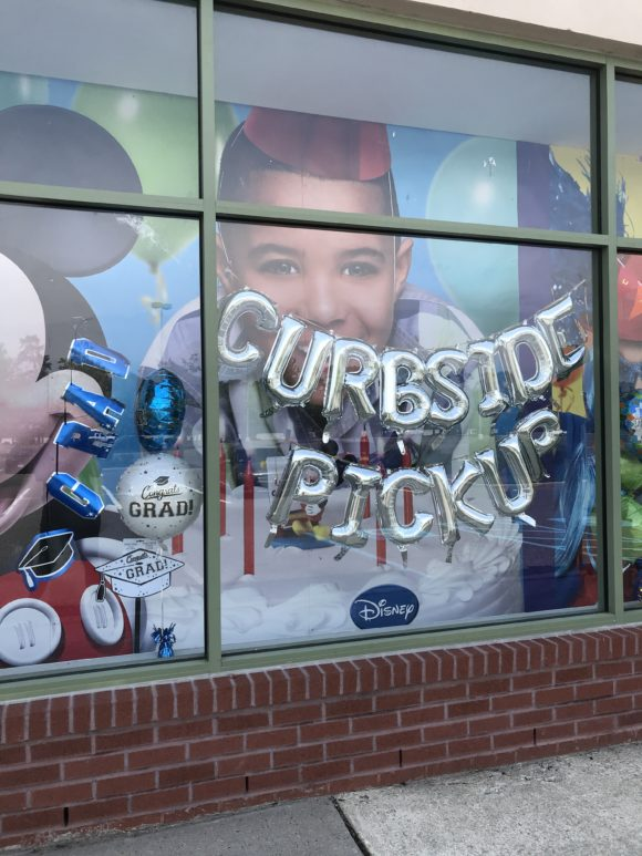 Facade of Party City showing they offer curbside service with balloons that spell it out.