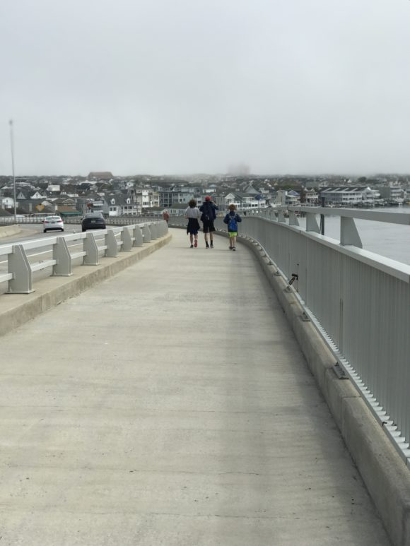 Three boys walk across the Ocean City bridge.