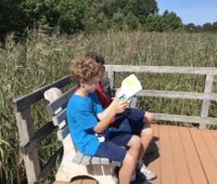 Boys sitting on bench at Cape May Point State Park
