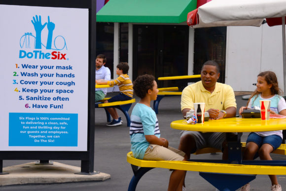 family sits at a table to eat at Six Flags Great Adventure