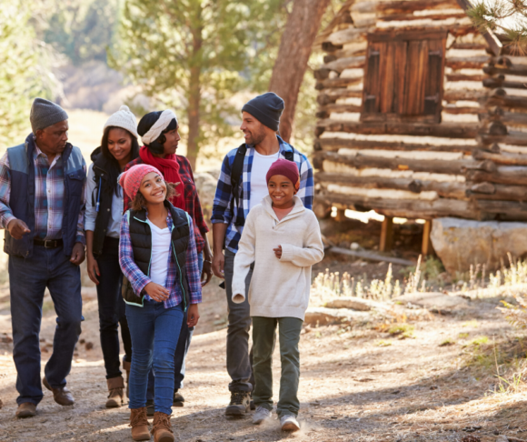 family walking in front of cabin