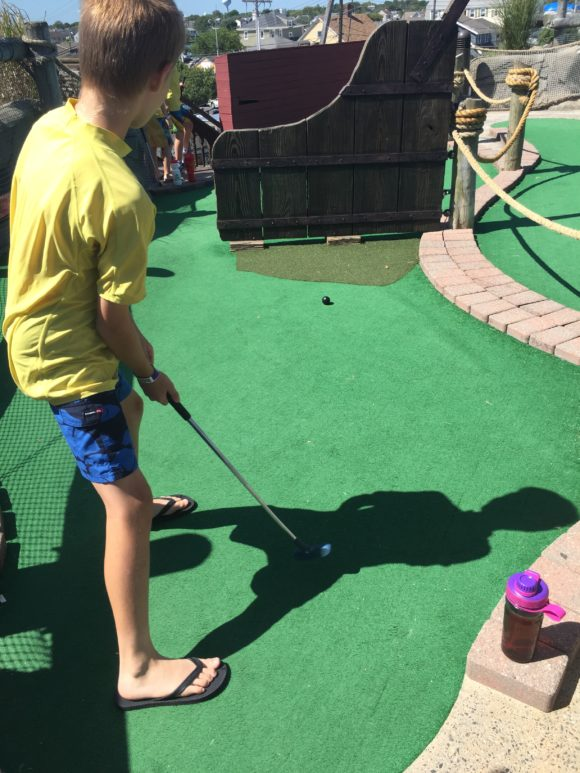 boy plays mini golf at the Jersey Shore, a great New Jersey outdoor activity