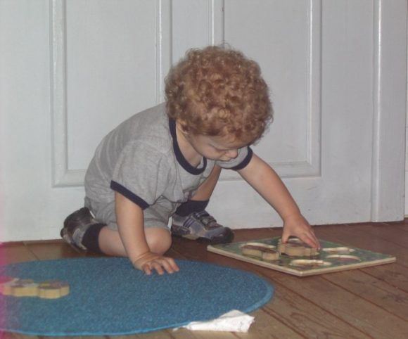 toddler works on a wood puzzle