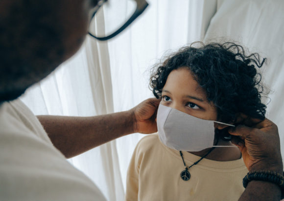 A father places a face mask on a child before sending him to school.