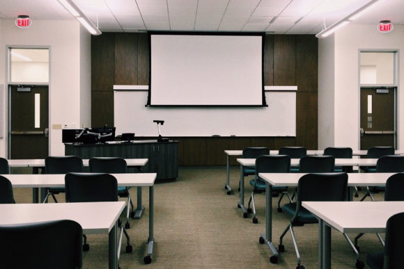 An empty NJ classroom with tables a whiteboard and a white screen.
