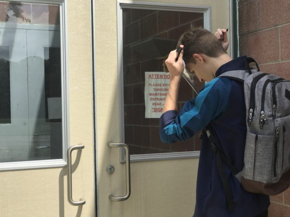a student straps on his Switlik clear face shield before heading into school.