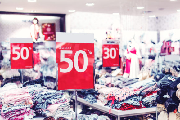 Photo of a store with tables of clothing and discount sale signs on top in red.
