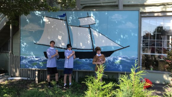 3 boys stand in front of a Tuckerton mural.