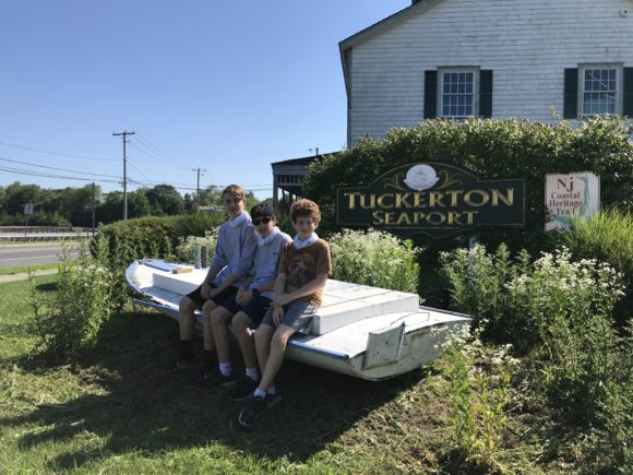 3 boys on a Tuckerton staycation take a picture in front of the Tuckerton Seaport.