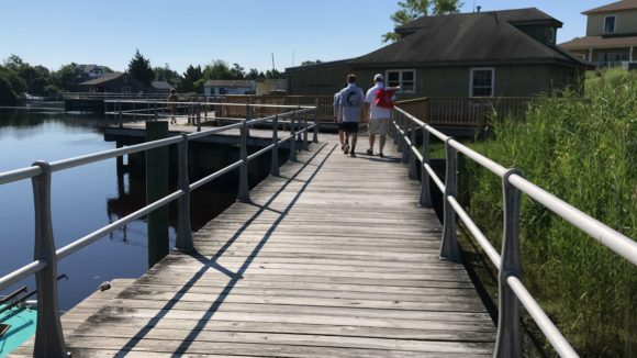A family walks on the Tuckerton Seaport boardwalk.