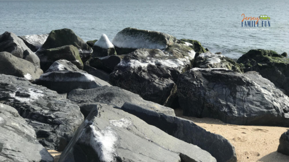 a picture of the rocks on Long Branch beach covered with some snow.