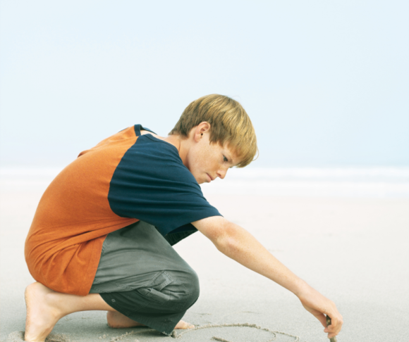 a boy practices his spelling lists by writing the spelling words in the sand.