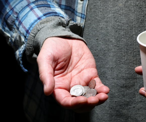 male with a handful of coins and a cup