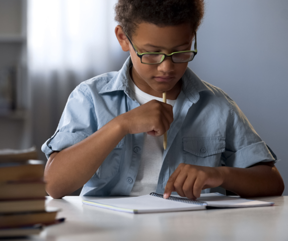 Black boy with glasses thinking about what he's writing in a notebook