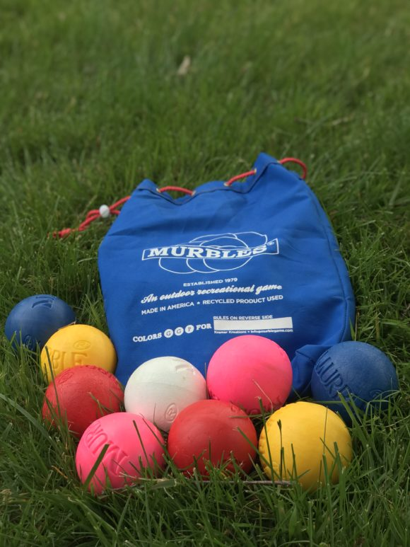 the murbles outdoor game balls and bags laying out in a backyard on grass