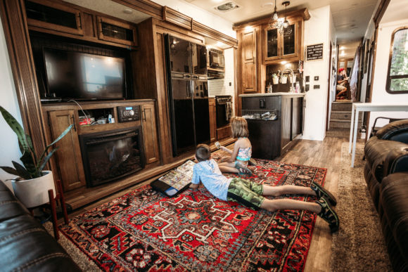 inside a luxurious RV rental kids stretch out to relax.
