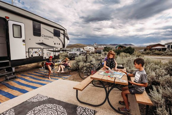 kids plays a board game while parents sit nearby and next to a trailer rv rental.