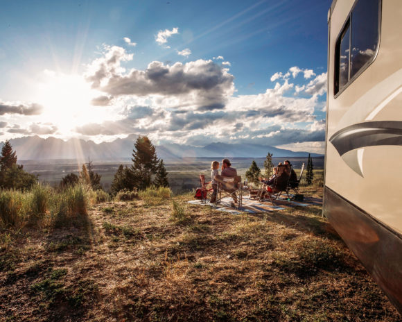 a family watches the sunrise in front of an RV trailer.