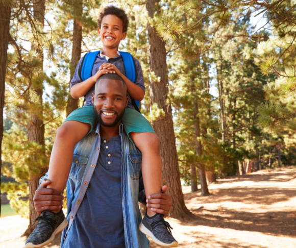 black father walking with son through the woods of a national park