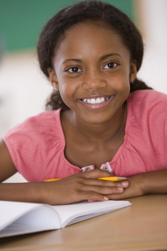 black girl looks up smiling while writing responses to writing prompts in a notebook