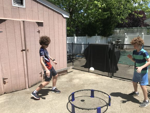 boys play smash ball in the backyard on pavement.