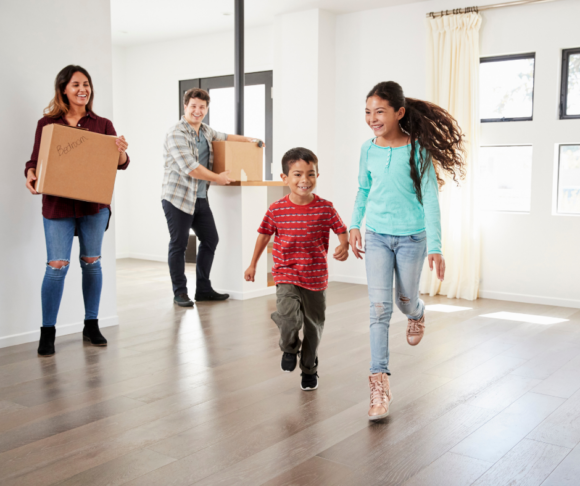 family moving into a new home in New Jersey. Parents holding moving boxes.