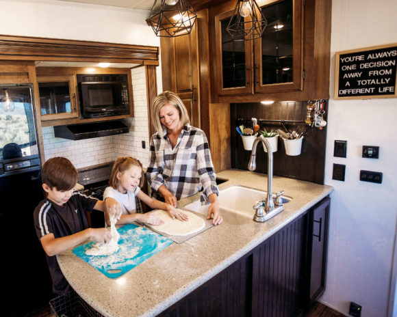 family makes pizza dough in an RV trailer kitchen.