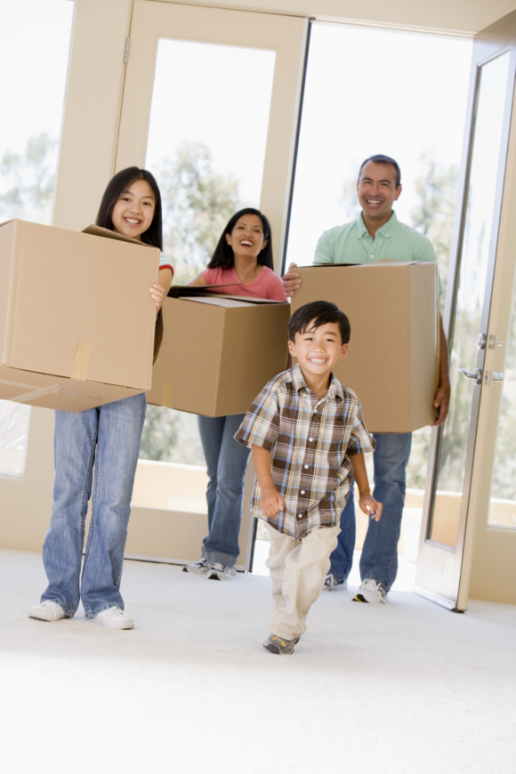 Asian family carries moving boxes into their new New Jersey home.
