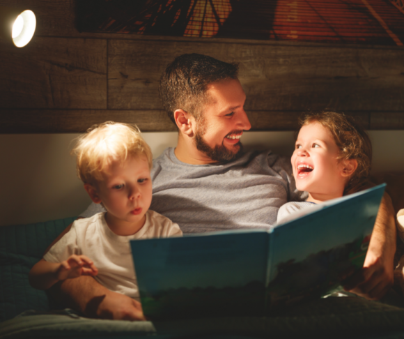father reads children a bedtime story