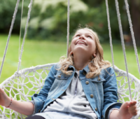 girl-in-netted-swing-in-backyard-looking-up