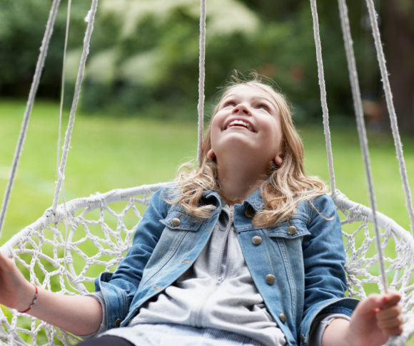 white Girl in a netted swing smiling and looking up.