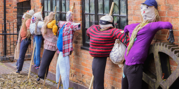 Horizontal image of 6 scarecrow robbers up against a building that is part of a New Jersey Scarecrows trail.